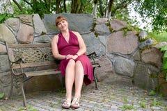 De vrouw van gemiddelde jaren zit op een decoratieve bank in het park royalty-vrije stock foto