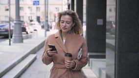 De vrouw van het Beautfiulblonde met koffie die en haar smartphone lopen gebruiken stock videobeelden