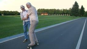 De vrouw van het echtgenootonderwijs aan skateboard in de zomerpark stock videobeelden