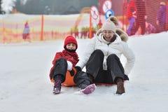 De vrouw van het familiemeisje het sledding op de sneeuw van de de winterheuvel stock foto