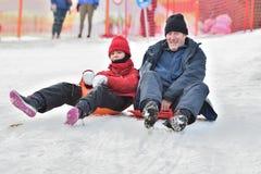 De vrouw van het familiemeisje het sledding op de sneeuw van de de winterheuvel royalty-vrije stock afbeeldingen