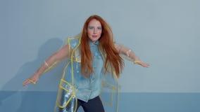 De vrouw van het gemberhaar in transparante regenjas met pop-art het heldere make-up dansen stock video