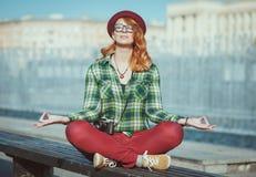 De vrouw van het Hipsterroodharige in hoed en glazen die yoga op de bank doen Royalty-vrije Stock Foto's