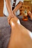 De Vrouw van het kuuroord De voet van de vrouw in het water De Massagetherapie van de benenolie De zorg van de huid stock fotografie