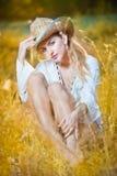 De vrouw van het manierportret met hoed en witte overhemdszitting op een hooistapel Stock Foto