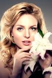 De vrouw van het schoonheidsgezicht, bloemen, lelie Meisjes gezond model in kuuroordsalo Royalty-vrije Stock Foto's