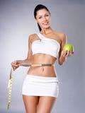 De vrouw van het vermageringsdieet met een metende band en een appel stock afbeelding