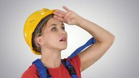 De vrouw van de ingenieursbouwvakker door de schaal van bouw op gradiëntachtergrond die wordt gefascineerd royalty-vrije stock foto