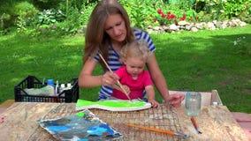 De vrouw van de kunstenaarsschilder met haar decoratie van de verf houten vissen van de kinddochter stock video