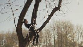 De vrouw van de luchtgymnastiek voert acrobatiektrucs op luchthoepel bij zonsopgang uit stock videobeelden