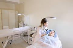 De vrouw van Nice bij de kosmetiekkabinet die het tatoeëren van wenkbrauwen door cosmetologist krijgen Royalty-vrije Stock Fotografie