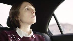 De vrouw van Nice met bruin haar in witte blouse en het kastanjebruine sweater berijden in auto en het bekijken venster stock footage