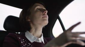 De vrouw van Nice met bruin haar in witte blouse en het kastanjebruine sweater berijden in auto en verklaren de juiste manier aan stock videobeelden