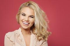 De vrouw van Nice met kapsel van het blonde het krullende loodje en mooie glimlach die pret hebben en tegen kleurrijke roze muura stock fotografie