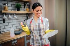 De vrouw van Nice in schorttribune in keuken en stelt Zij houdt witte plaat en glimlach Professionele vrouwelijke reinigingsmachi stock foto's