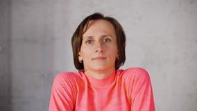 De vrouw van de portretgeschiktheid de gymnastiek van opleidingsschouders op witte achtergrond in studio Sportvrouw die oefening  stock videobeelden