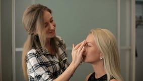 De vrouw van de schoonheidszaal A past een blondestichting op haar huid toe stock footage