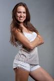 De vrouw van Smiley in pyjama's tegen grijze achtergrond Royalty-vrije Stock Foto