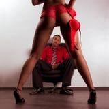 De vrouw van Striper in het rode dansen voor de jonge zwarte mens Stock Afbeeldingen