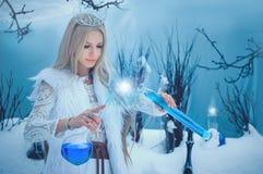 De Vrouw van de de winterschoonheid Mooi mannequinmeisje met het kapsel en de samenstelling van glasflessen in de winterlaborator stock afbeeldingen