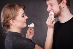 De vrouw veegt man gezicht door hygiënisch weefsel af stock afbeelding