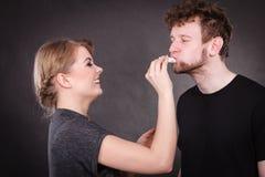 De vrouw veegt man gezicht door hygiënisch weefsel af royalty-vrije stock afbeeldingen