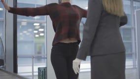 De vrouw verborg telefoon onder blouse en didn gaat ` t door de controlepost bij de luchthaven stock footage