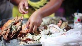 De vrouw verdeelt een gekookte krab op nachtmarkt voor verkoop 1920x1080 stock videobeelden