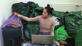 De vrouw verdeelt kleren en maakt ingangen op laptop stock videobeelden
