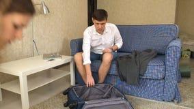 De vrouw verdrijft de dronken echtgenoot, verzamelt zijn dingen in een koffer scheiding stock footage