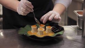De vrouw verfraait bereid gerecht die zich door lijst in keuken bevinden stock footage