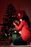 De vrouw verfraait Kerstboom in nacht Stock Afbeeldingen