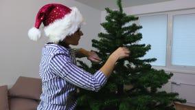 De vrouw verfraait kunstmatige Kerstboom stock video