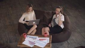 De vrouw verklaart de nieuwe werknemer wat met grafiek te doen stock videobeelden