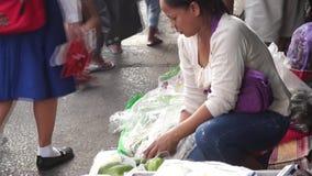 De vrouw verkoopt groenten langs stadsstoep stock footage