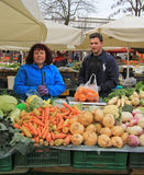 De vrouw verkoopt groenten op de straatmarkt in Ljubljana, Slovenië stock foto