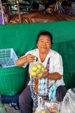 De vrouw verkoopt vruchten bij de markt Royalty-vrije Stock Afbeelding