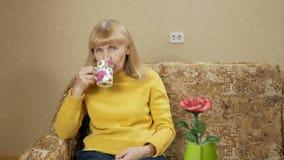 De vrouw verouderde thuis het drinken van een hete drank van een kop op de laag en het bekijken de camera Zij rust na hard stock videobeelden