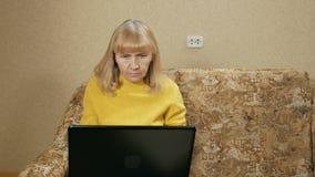 De vrouw verouderde zorgvuldig de werken bij laptop thuis op de laag Zij typt op toetsenbord en bekijkt het scherm E stock footage