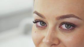 De vrouw verplaatst haar starende blik bij de de kosmetieksalon stock foto's