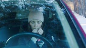 De vrouw verwarmt haar indient de auto in het hout Koud de winterconcept stock footage