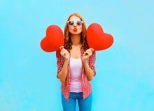 de vrouw verzendt een luchtkus met rode ballons in de vorm van een hart Stock Afbeeldingen