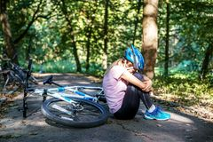 De vrouw viel van een fiets in een helm trauma Het concept o Stock Afbeeldingen