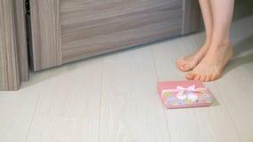 De vrouw vindt een gift onder de deur stock videobeelden