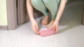 De vrouw vindt een gift onder de deur stock footage