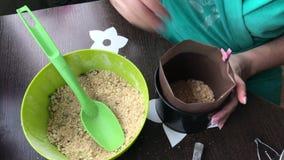 De vrouw voegt biscuitgebak aan cake vorm toe Verzegelt de laag met een houten deegrol Het koken van een cake van koekjescrumbs e stock footage