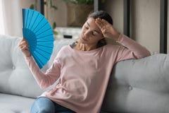 De vrouw voelt ongemak van hitte golvend blauwe te koelen ventilator stock fotografie