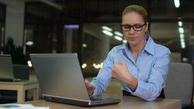 De vrouw voelt polspijn die door bovenmatig gebruik van laptop wordt veroorzaakt, carpal tunnel syndrome stock footage