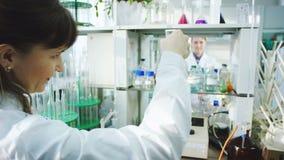 De vrouw voert chemische test door fles met vloeistof uit te schudden stock footage