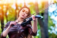 De vrouw voert muziek op vioolpark openluchtuit Meisje die jazz uitvoeren royalty-vrije stock afbeeldingen